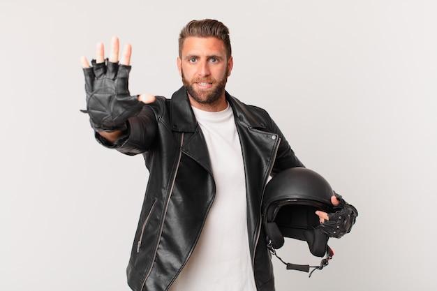 Młody przystojny mężczyzna uśmiechnięty i przyjazny, pokazując numer pięć. koncepcja kasku motocyklowego