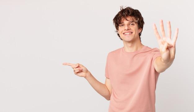 Młody przystojny mężczyzna uśmiechnięty i wyglądający przyjaźnie, pokazujący cyfrę cztery