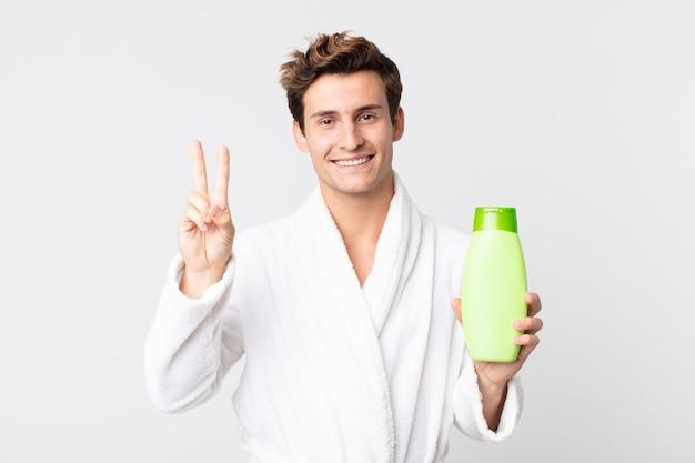 Młody przystojny mężczyzna uśmiechnięty i wyglądający przyjaźnie, pokazujący numer dwa w szlafroku i trzymający butelkę szamponu