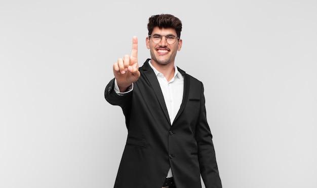 Młody przystojny mężczyzna uśmiechnięty i wyglądający przyjaźnie, pokazujący numer jeden lub pierwszy z ręką do przodu, odliczający