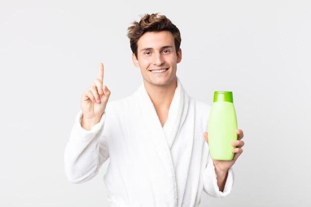Młody przystojny mężczyzna uśmiechnięty i wyglądający przyjaźnie, pokazujący numer jeden w szlafroku i trzymający butelkę szamponu
