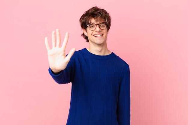 Młody przystojny mężczyzna uśmiechnięty i wyglądający przyjaźnie, pokazujący numer pięć