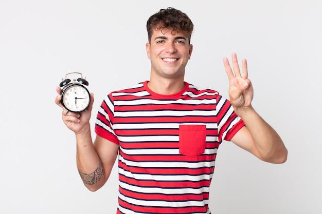 Młody przystojny mężczyzna uśmiechnięty i wyglądający przyjaźnie, pokazujący numer trzy i trzymający budzik