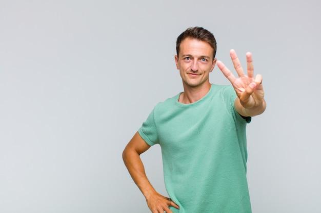 Młody przystojny mężczyzna uśmiechnięty i wyglądający przyjaźnie, pokazujący numer trzy lub trzeci z ręką do przodu, odliczający