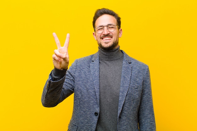 Młody przystojny mężczyzna uśmiechnięty i wyglądający przyjazny, pokazując numer dwa lub drugi ręką do przodu, odliczając do ściany pomarańczowy