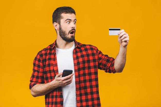 Młody przystojny mężczyzna używa smartphone odizolowywającego okaleczającego w szoku z niespodzianki twarzą, przestraszonego i podekscytowanego wyrażeniem strachu kartą kredytową, robi zakupy.