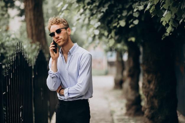 Młody przystojny mężczyzna używa telefon out na ulicie