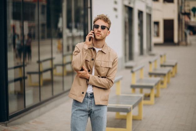 Młody przystojny mężczyzna używa telefon outside w ulicie