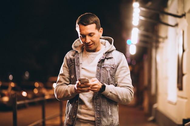 Młody przystojny mężczyzna używa telefon przy nocą w ulicie
