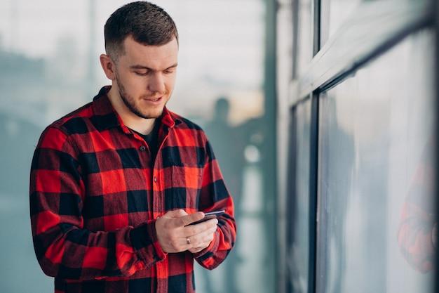 Młody przystojny mężczyzna używa telefon