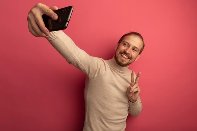 Młody przystojny mężczyzna w beżowym golfie za pomocą smartfona robi selfie, uśmiechając się, pokazując znak v