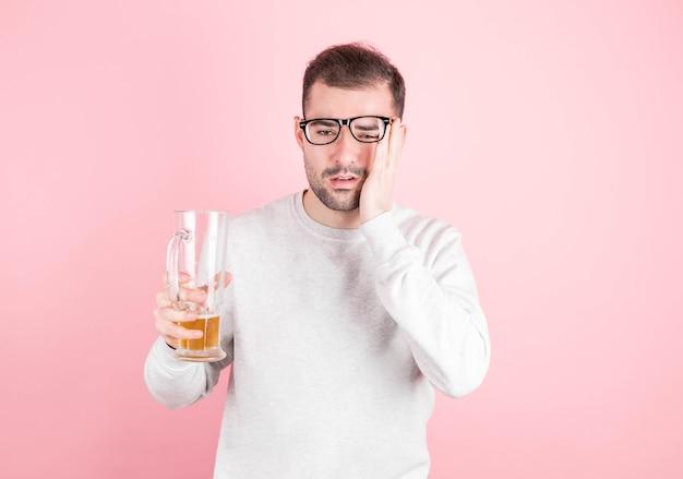 Młody przystojny mężczyzna w białej bluzie zmarzł po przyjęciu. koncepcja kaca i alkoholizmu.