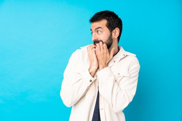 Młody przystojny mężczyzna w białej sztruksowej kurtce na pojedyncze niebieskie ściany nerwowe i przestraszony, kładzenie rąk do buzi