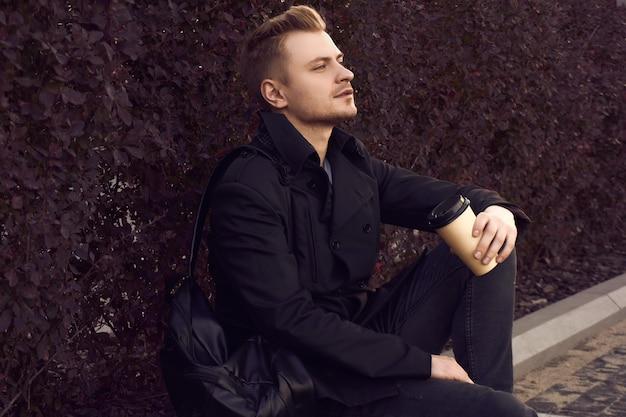 Młody przystojny mężczyzna w ciemnym płaszczu z filiżanką kawy