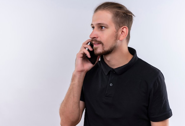 Młody przystojny mężczyzna w czarnej koszulce polo patrząc na bok, uśmiechając się, rozmawiając na telefon komórkowy stojący na białym tle