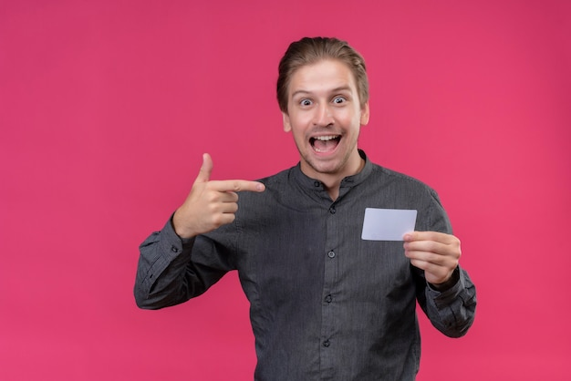 Młody przystojny mężczyzna w czarnej koszuli, trzymając telefon komórkowy, wskazując palcem na to