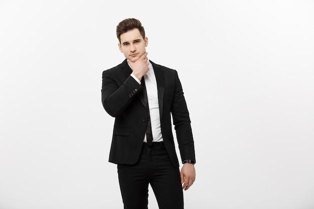 Młody przystojny mężczyzna w czarnym garniturze i okularach patrzący na copyspace myślący lub śniący na białym tle nad...