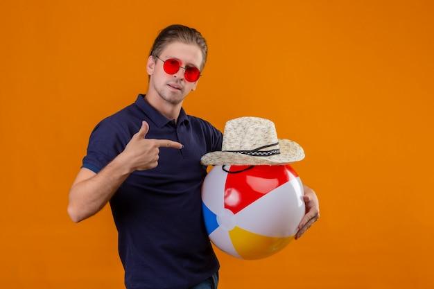 Młody przystojny mężczyzna w czerwonych okularach przeciwsłonecznych, trzymając nadmuchiwaną piłkę i letni słomkowy kapelusz, wskazując palcem na aparat, patrząc na kamerę z pewnym siebie wyrazem twarzy stojącej na pomarańczowym tle