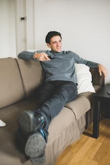 Młody przystojny mężczyzna w domu siedzi w domu, oglądając telewizję, trzymając pilota zdalnego sterowania
