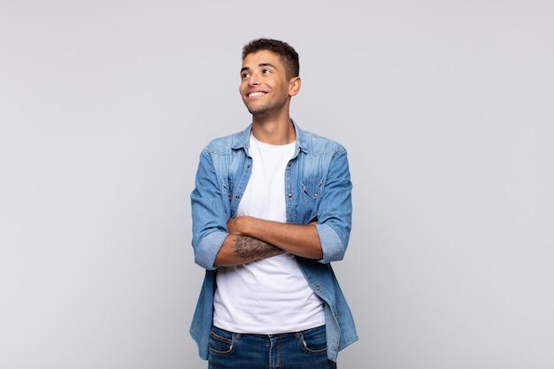 Młody przystojny mężczyzna w dżinsowej koszuli pozuje na białej ścianie