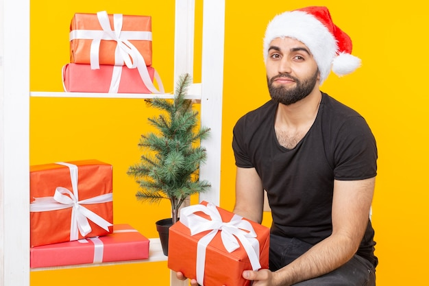 Młody przystojny mężczyzna w kapeluszu świętego mikołaja trzyma gratulacyjne prezenty obok choinki. koncepcja świąt bożego narodzenia i nowego roku.