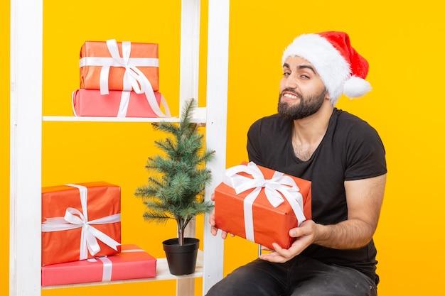 Młody przystojny mężczyzna w kapeluszu świętego mikołaja trzyma obok choinki gratulacyjne prezenty