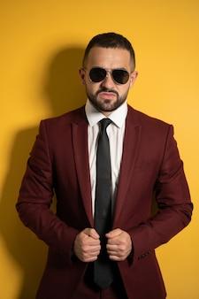 Młody przystojny mężczyzna w kolorze bordowym, patrząc na ciebie poważnie w okularach przeciwsłonecznych z rękami trzymającymi kurtkę na białym tle na żółtej ścianie
