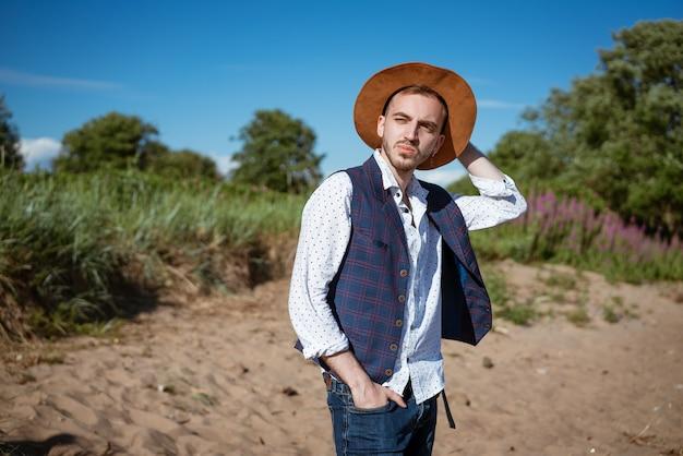 Młody przystojny mężczyzna w koszuli i kapeluszu na naturze wygląda z boku w ciągu dnia w lecie