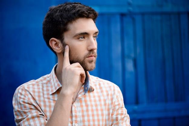 Młody przystojny mężczyzna w kraciastej koszuli myślenia