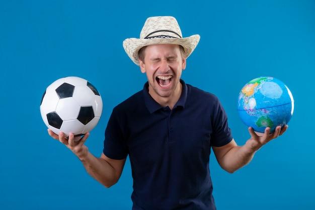 Młody przystojny mężczyzna w letnim kapeluszu trzyma piłkę nożną i kula ziemska szalony szczęśliwy krzyczy w fascynacji stojąc na niebieskim tle