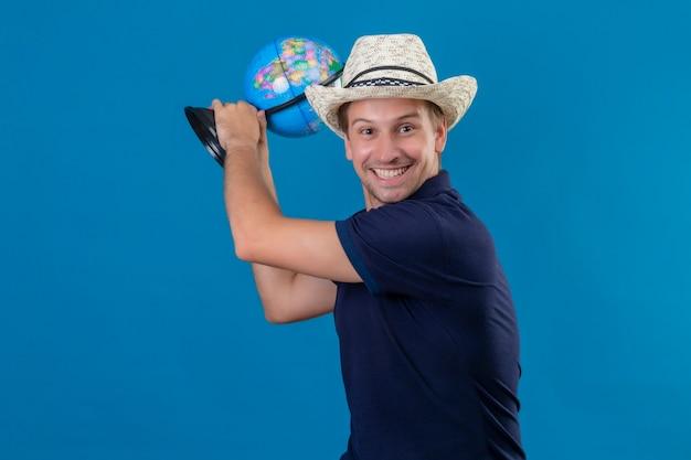 Młody przystojny mężczyzna w letnim kapeluszu trzymając kulę ziemską grożą uderzeniem kulą ziemską, żartując i uśmiechając się stojąc na niebieskim tle