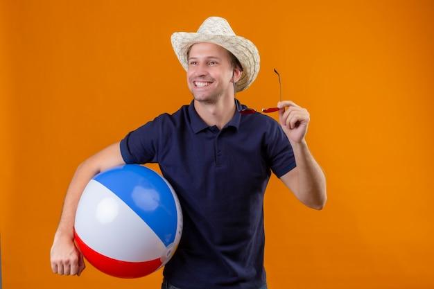 Młody przystojny mężczyzna w letnim kapeluszu, trzymając nadmuchiwaną piłkę i okulary przeciwsłoneczne, uśmiechając się radośnie z szczęśliwą twarzą stojącą na pomarańczowym tle