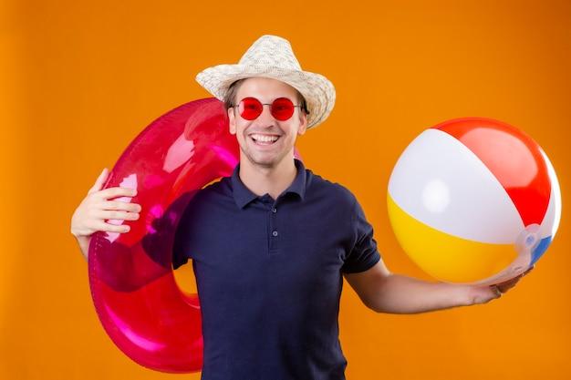 Młody przystojny mężczyzna w letnim kapeluszu w czerwonych okularach przeciwsłonecznych, trzymając nadmuchiwaną piłkę i pierścionek, patrząc na kamerę z pewnym siebie uśmiechem, zadowolony z siebie i szczęśliwy stojąc na pomarańczowym tle