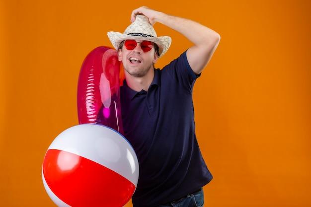 Młody przystojny mężczyzna w letnim kapeluszu w czerwonych okularach przeciwsłonecznych trzymający nadmuchiwaną piłkę i pierścionek patrząc na kamerę z pewnym siebie uśmiechem zadowolona z siebie pozycja na pomarańczowym tle