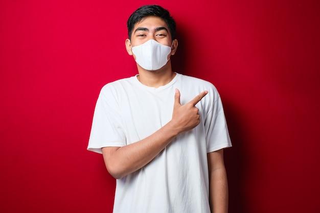 Młody przystojny mężczyzna w masce medycznej uśmiechający się i patrzący w kamerę wskazującą jedną ręką i palcami w bok na czerwonym tle