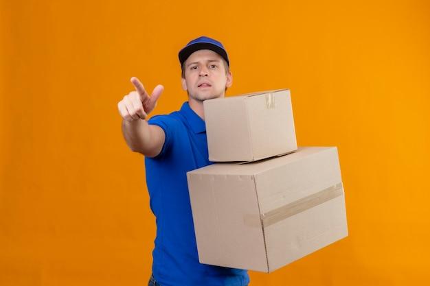Młody przystojny mężczyzna w niebieskim mundurze i czapce trzyma kartony, wskazując na coś palcem
