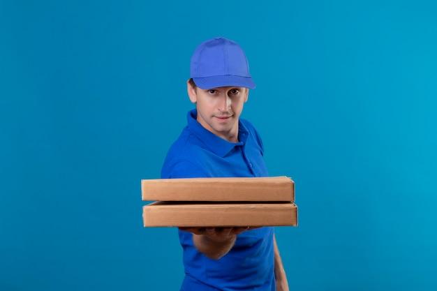 Młody przystojny mężczyzna w niebieskim mundurze i czapce trzyma pudełka po pizzy z pewnym uśmiechem na twarzy stojącej nad niebieską ścianą