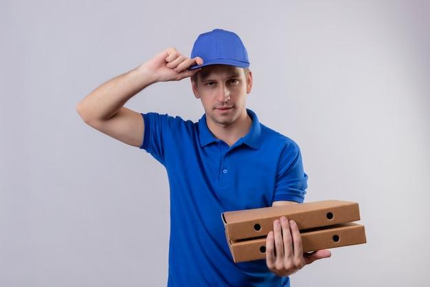 Młody przystojny mężczyzna w niebieskim mundurze i czapce trzyma pudełka po pizzy z pewnym wyrazem twarzy stojącej nad białą ścianą
