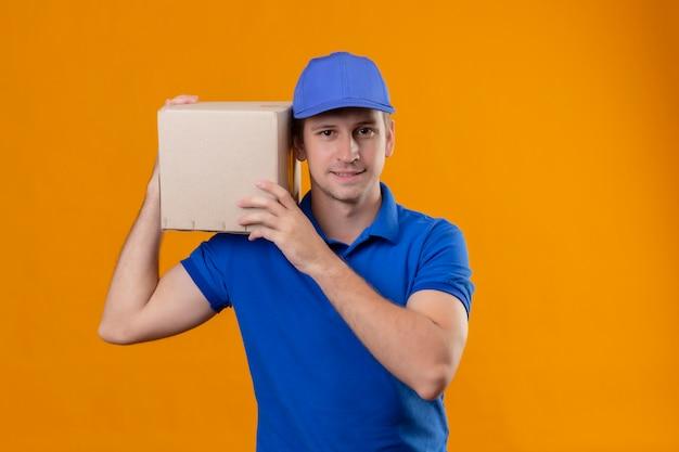 Młody przystojny mężczyzna w niebieskim mundurze i czapce trzyma pudełko na ramieniu, patrząc pewnie