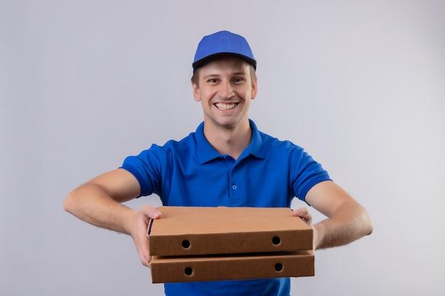 Młody przystojny mężczyzna w niebieskim mundurze i czapce, trzymając pudełka po pizzy uśmiechnięty przyjazny stojący nad białą ścianą