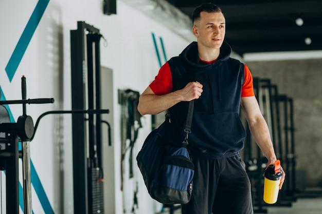 Młody przystojny mężczyzna w odzieży sportowej na siłowni
