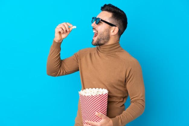 Młody przystojny mężczyzna w okularach 3d i gospodarstwa duże wiadro popcorns