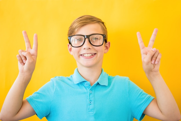 Młody przystojny mężczyzna w okularach na białym tle uśmiechnięty, patrząc do kamery pokazując palce robi znak zwycięstwa. numer dwa