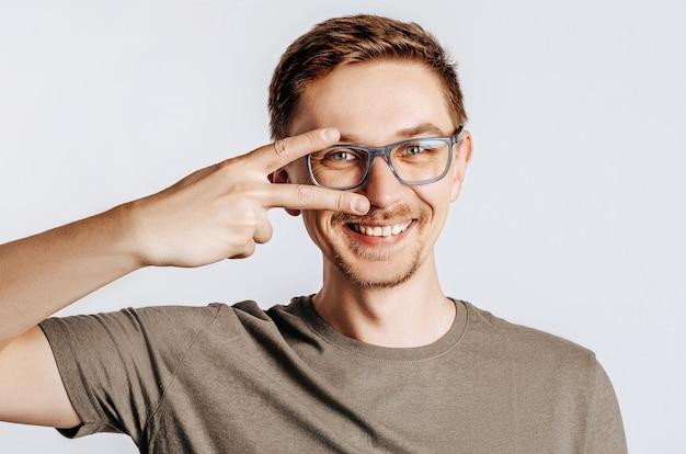 Młody przystojny mężczyzna w okularach robi symbol pokoju z palcami na twarzy, uśmiechając się wesoło, pokazując zwycięstwo. przystojny facet uśmiecha się na na białym tle szarym tle. miejsce na reklamę.