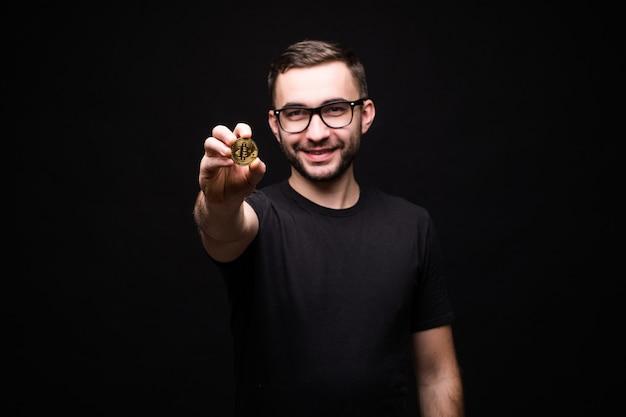 Młody przystojny mężczyzna w okularach w czarnej koszuli wskazał złoty bitcoin na aparat odizolowany na czarno