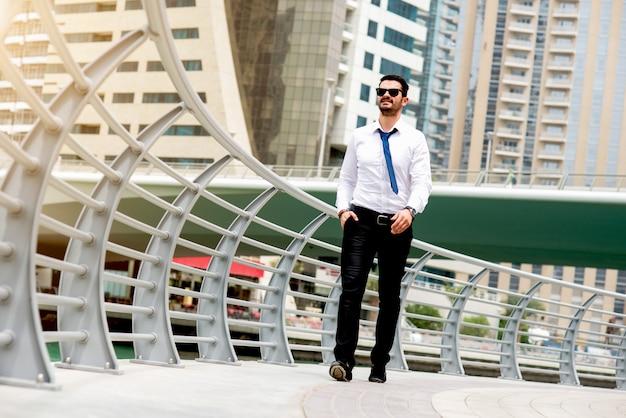 Młody przystojny mężczyzna w pełnym kolorze idąc ulicą uśmiecha się