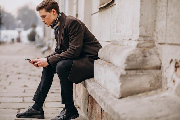 Młody przystojny mężczyzna w płaszczu na zewnątrz ulicy za pomocą telefonu