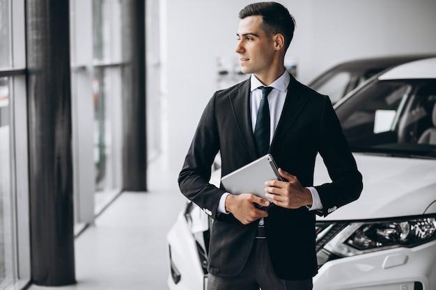 Młody przystojny mężczyzna w salonie samochodowym