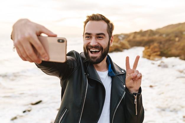 Młody przystojny mężczyzna w skórzanej kurtce robi zdjęcie selfie na smartfonie podczas spaceru nad morzem