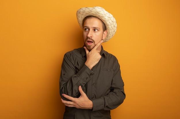 Młody przystojny mężczyzna w szarej koszuli i letnim kapeluszu patrząc na bok z ręką na brodzie zaskoczony